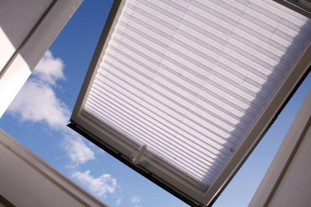 Dachfenster geben den Blick in die Landschaft und den Himmel frei, wodurch eine helle und großzügige Atmosphäre entsteht.