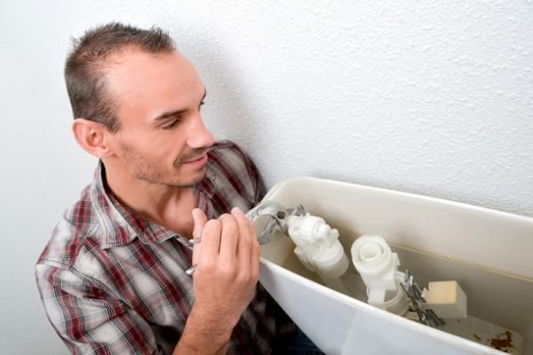 Mann am WC Spülkasten