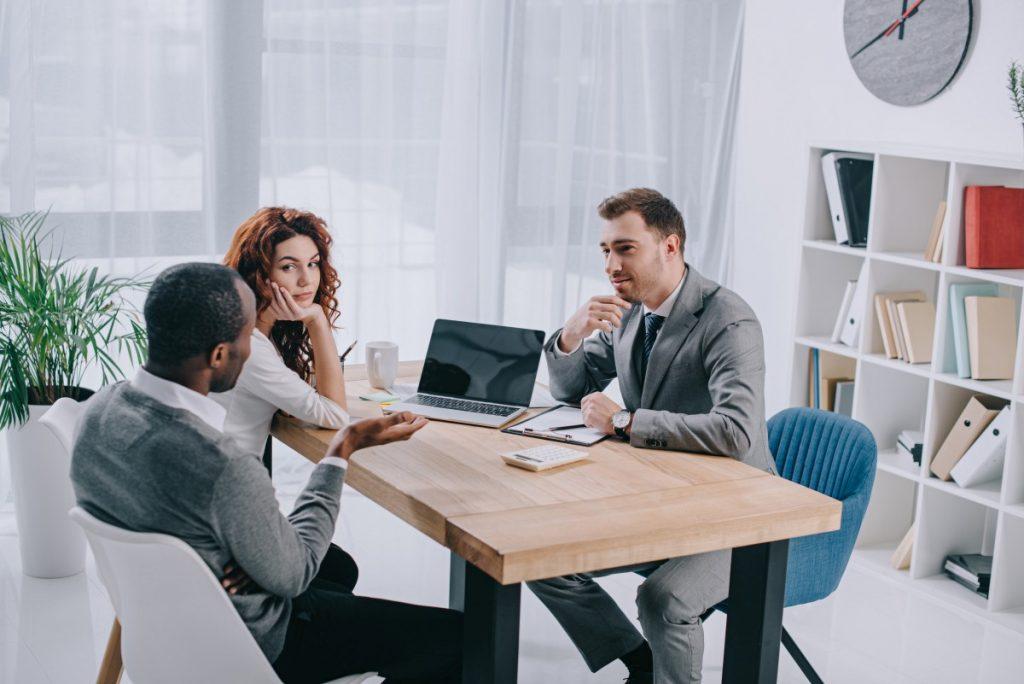 Immobilienmakler mit Kunden an einem Tisch